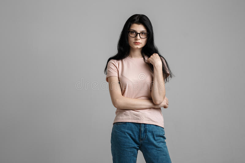 Portrait of smart beautiful brunette girl in eyeglasses with natural make-up, on grey background. royalty free stock image