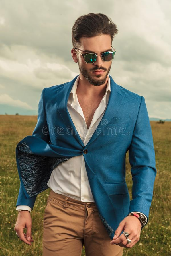 Portrait of smart casual man on cloudy weather outside. Portrait of smart casual man wearing a blue suit and sunglasses standing in a field on cloudy weather stock photography