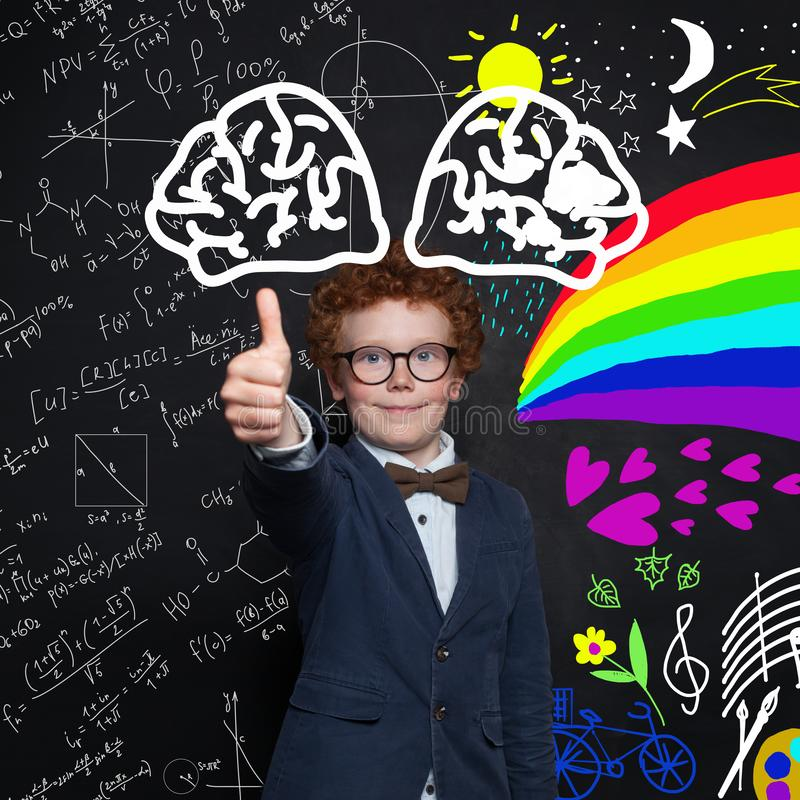 Portrait of smart child in suit and glasses. Clever kid student holding thumb up on science and arts pattern background royalty free stock photography