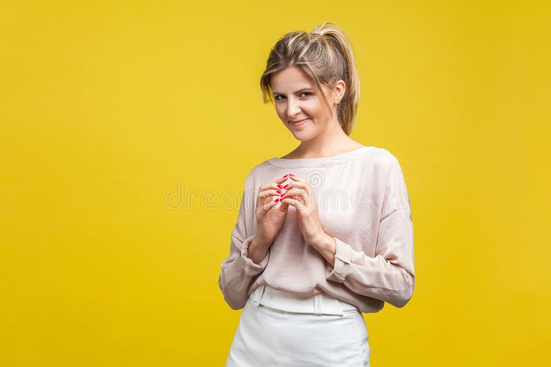 Portrait of smart cunning young woman with fair hair in casual beige blouse, isolated on yellow background. Portrait of smart cunning young woman with fair hair stock images