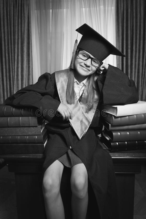 Portrait of smart girl in graduation cap posing on table at libr. Black and white portrait of smart girl in graduation cap posing on table at library royalty free stock photography