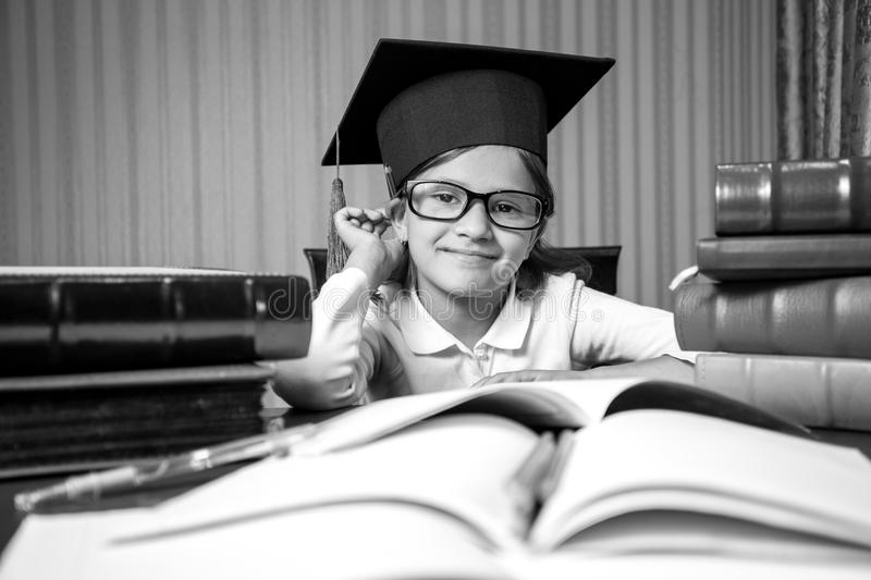 Portrait of smart girl in graduation hat sitting at desk full of. Black and white portrait of smart girl in graduation hat sitting at desk full of books stock photo