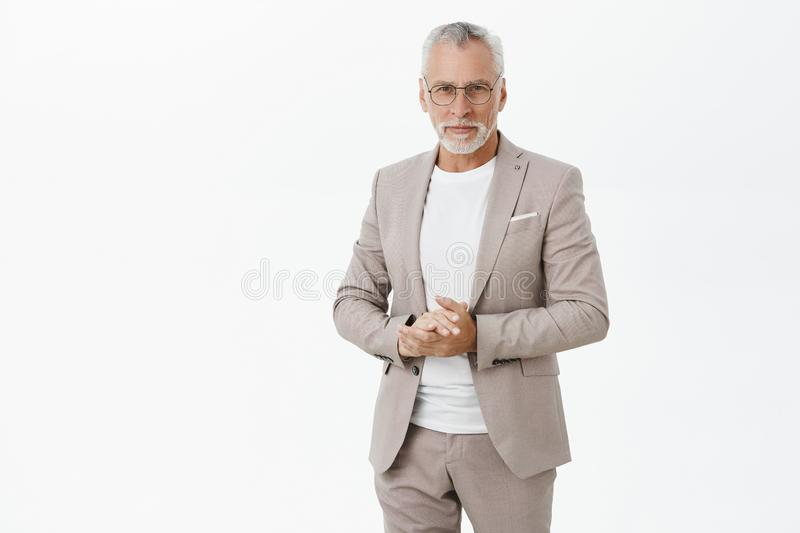 Portrait of smart and handsome intelligent senior male professor in stylish suit and glasses holding hands together stock photography