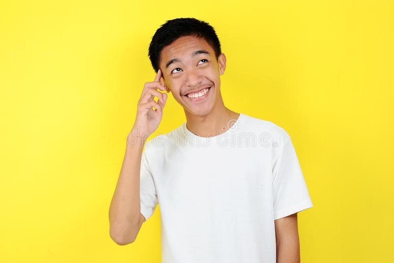 Portrait of smart and happy young Asian man thinking and look up. Happy young Asian man wearing white t-shirt thinking and look up royalty free stock photos