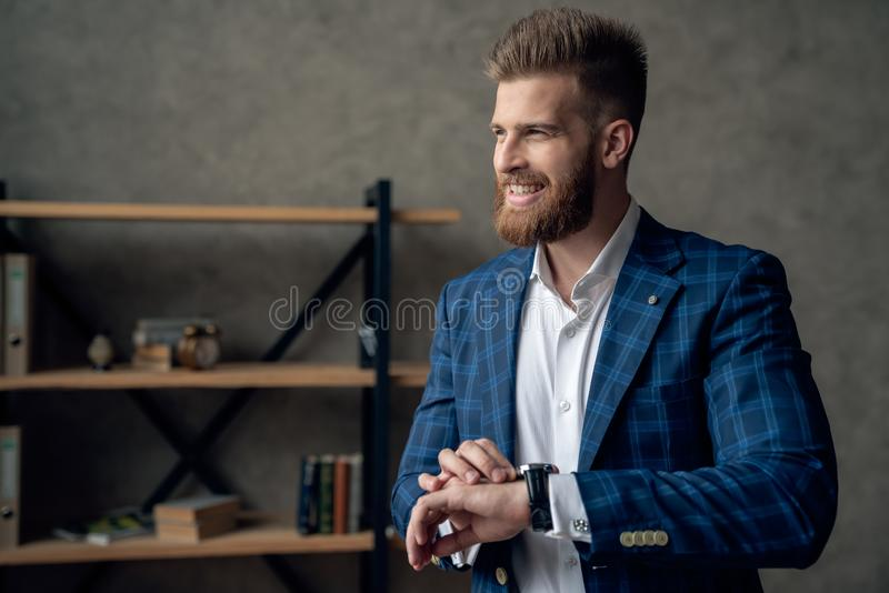 Portrait of smart responsible man with modern hairdo looking at watch on wrist over blurred office hurry up for meeting. Management employment job concept stock photos