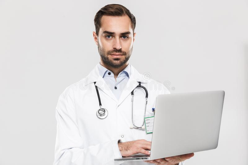 Portrait of smart young medical doctor with stethoscope working in clinic and holding laptop royalty free stock image