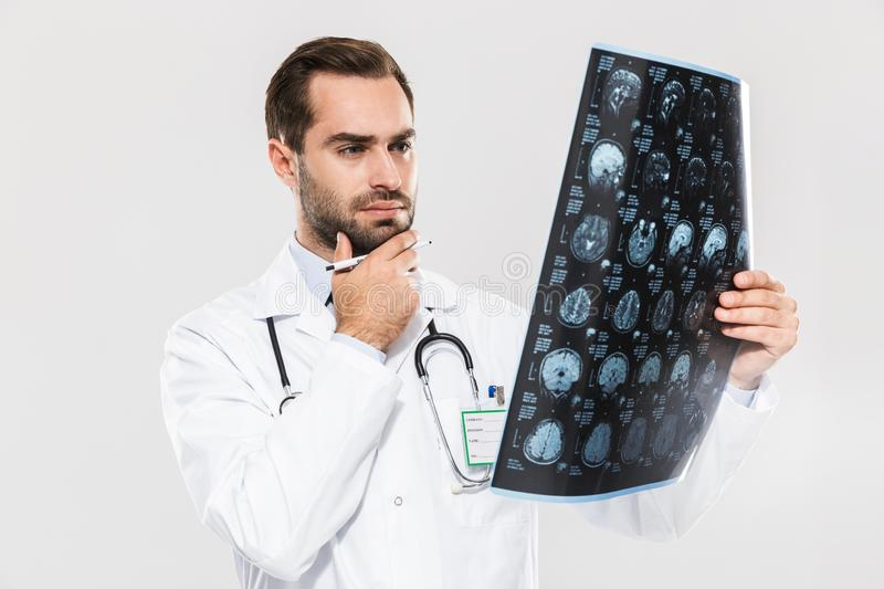Portrait of smart young medical doctor working in hospital and holding X-ray scan stock photography