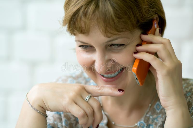 Portrait smile of a middle-aged woman talking on the phone. Close-up royalty free stock photography