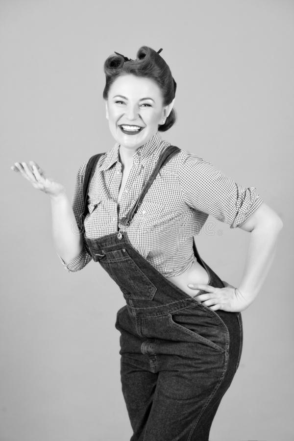 Portrait of smiled and cheerful pin-up girl standing with hand. Portrait of smiled and cheerful pin-up girl standing with arm on hips and holding copy space on royalty free stock photos
