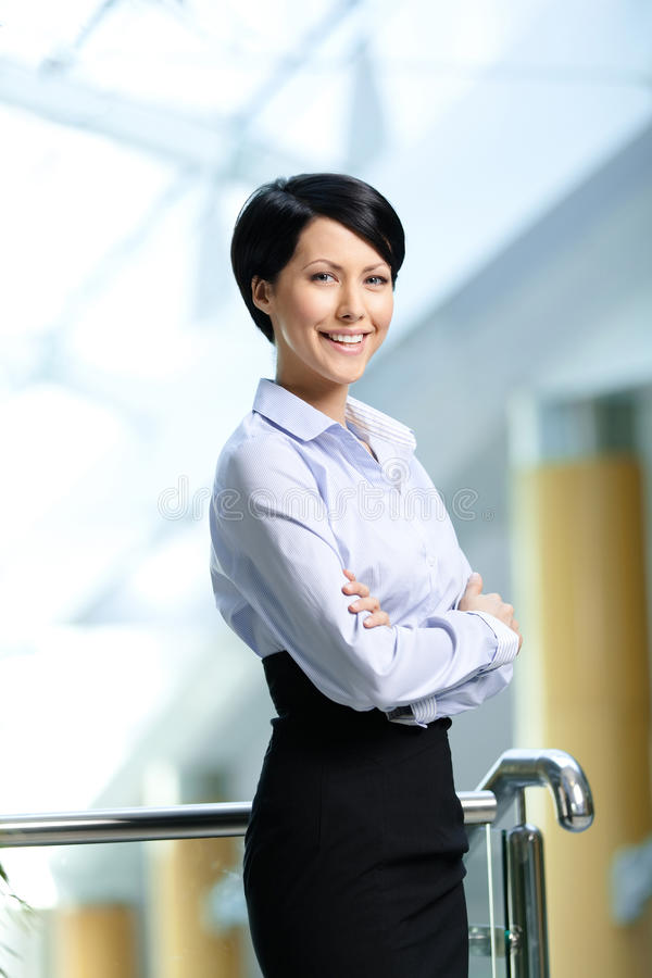 Portrait of a smiley businesswoman. With arms crossed wearing white shirt and black skirt at business centre stock images
