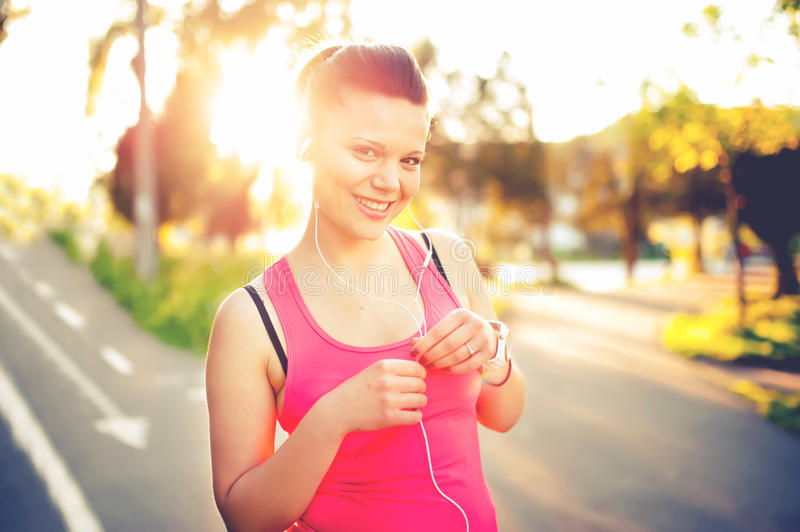 Portrait of a smiling active female runner, resting from jogging royalty free stock photography