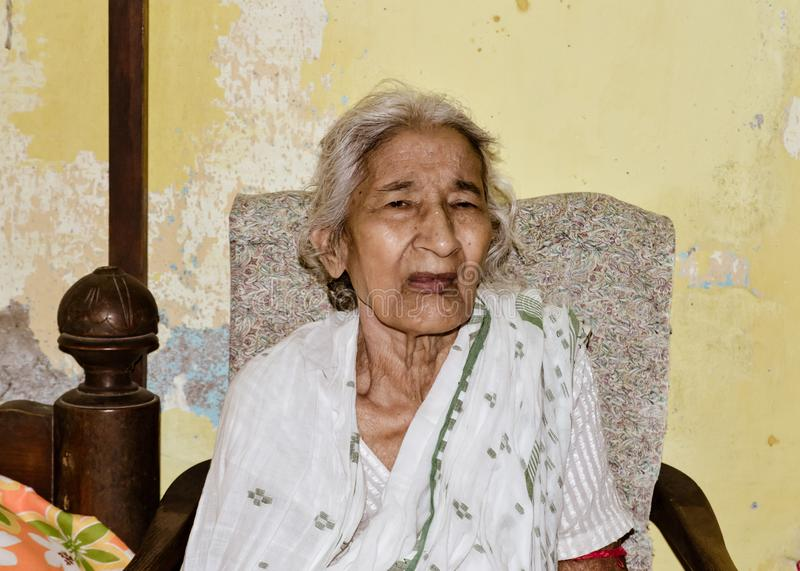 Portrait of smiling Active senior Asian and Indian Ethnicity woman of 82 years sitting on chair resting at home while looking at royalty free stock image