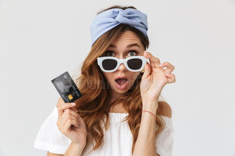 Portrait of smiling adorable woman 20s wearing sunglasses holding credit card, isolated over white background stock photos