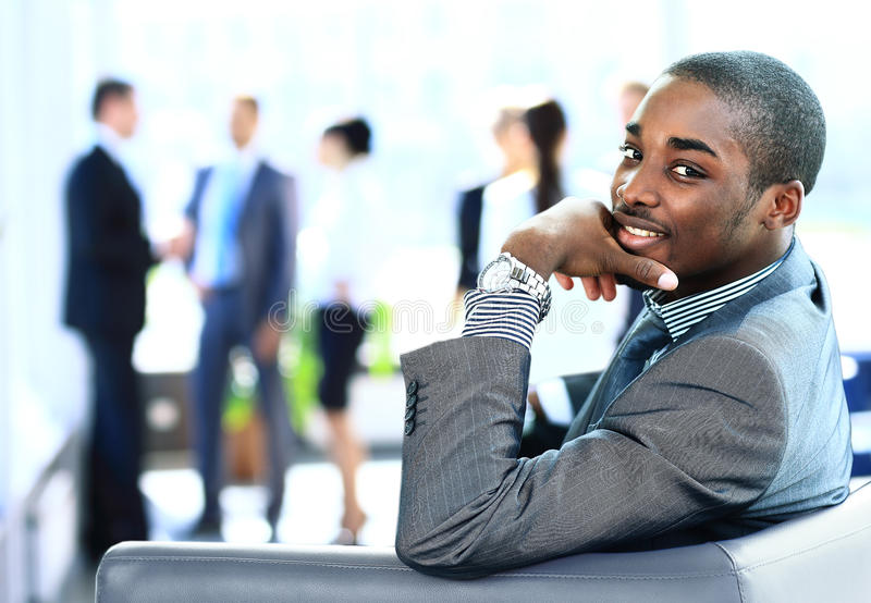 Portrait of smiling African American business. Man with executives working in background royalty free stock images