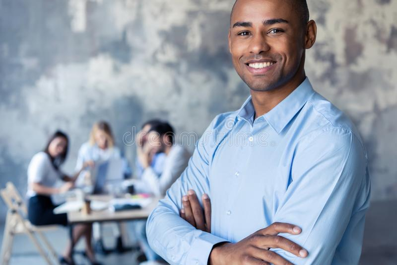Portrait of smiling African American business man with executives working in background. Portrait of smiling African American business men with executives stock photo