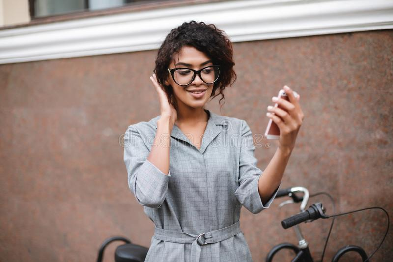 Smiling African American girl in glasses standing with cellphone in hand. Young beautiful lady with dark curly hair in. Portrait of smiling African American girl royalty free stock photography