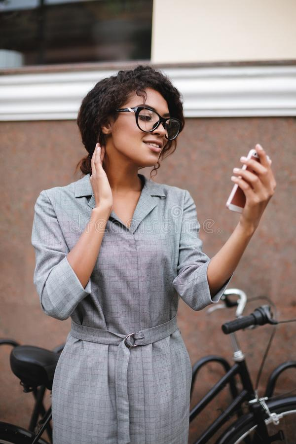 Smiling African American girl in glasses standing with cellphone in hand. Young pretty lady with dark curly hair in gray. Portrait of smiling African American royalty free stock images