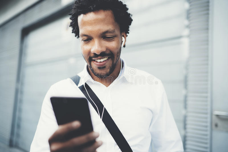 Portrait of Smiling African American man in headphones standidng in sunny street listening to songs on his mobile phone royalty free stock photography