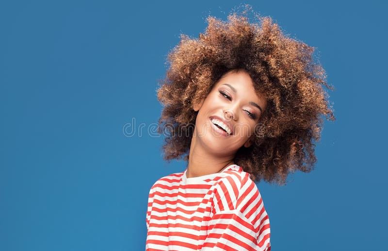 Smiling afro woman in sailor style shirt. Portrait of smiling african american woman posing on blue background, wearing shirt in white and red stripes, sailor stock photos