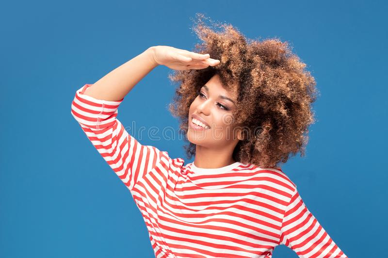 Smiling afro woman in sailor style shirt. Portrait of smiling african american woman posing on blue background, wearing shirt in white and red stripes, sailor stock images