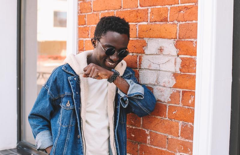 Portrait smiling african man with smart watch using voice command recorder or takes calling on city street, brick wall. Background royalty free stock image
