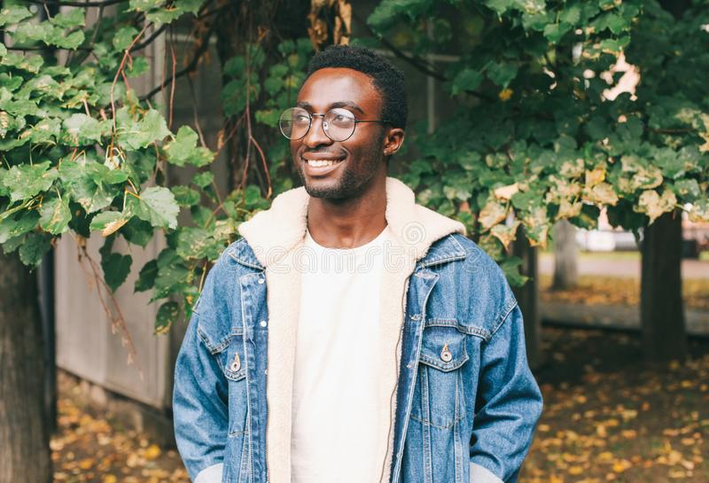 Portrait smiling african man wearing jeans jacket, eyeglasses in autumn city park stock images