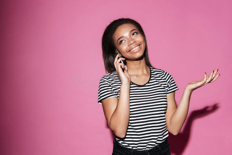 Portrait of a smiling african woman talking on mobile phone royalty free stock image