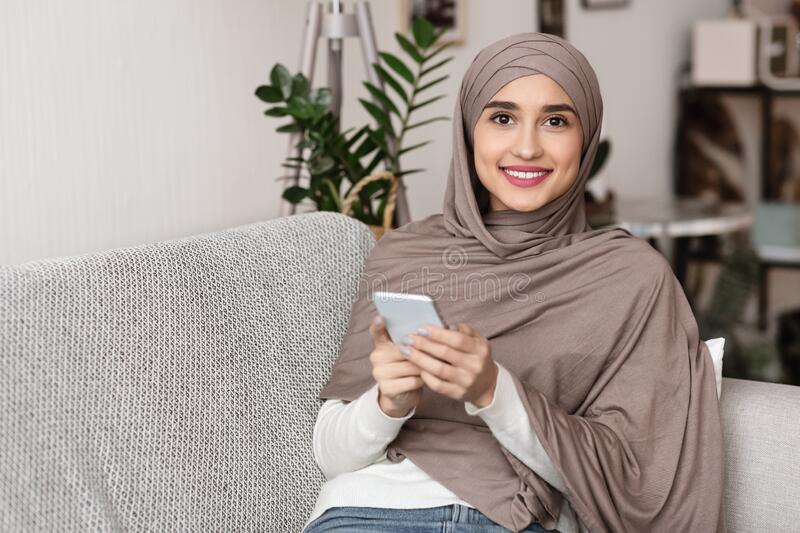 Portrait of smiling arabic girl in headscarf using smartphone at home royalty free stock image
