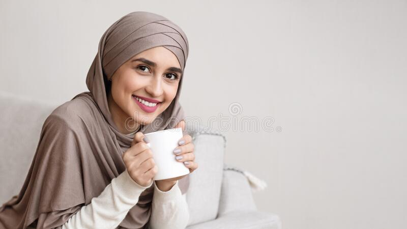 Portrait of smiling arabic girl in hijab drinking tea at home royalty free stock photo