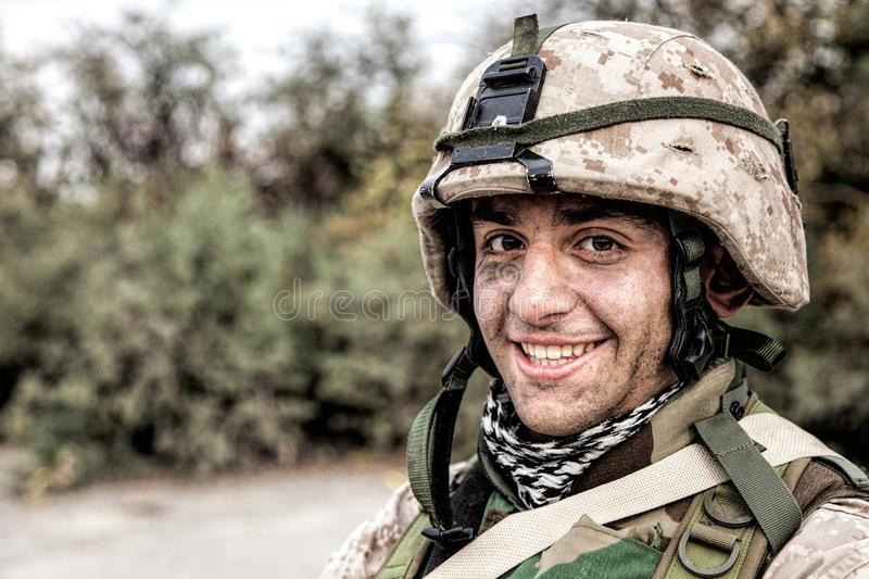 Portrait of smiling army soldier in ragged helmet. Shoulder portrait of happy smiling young soldier in battle helmet with scratches on camouflage, equipped U.S stock photography