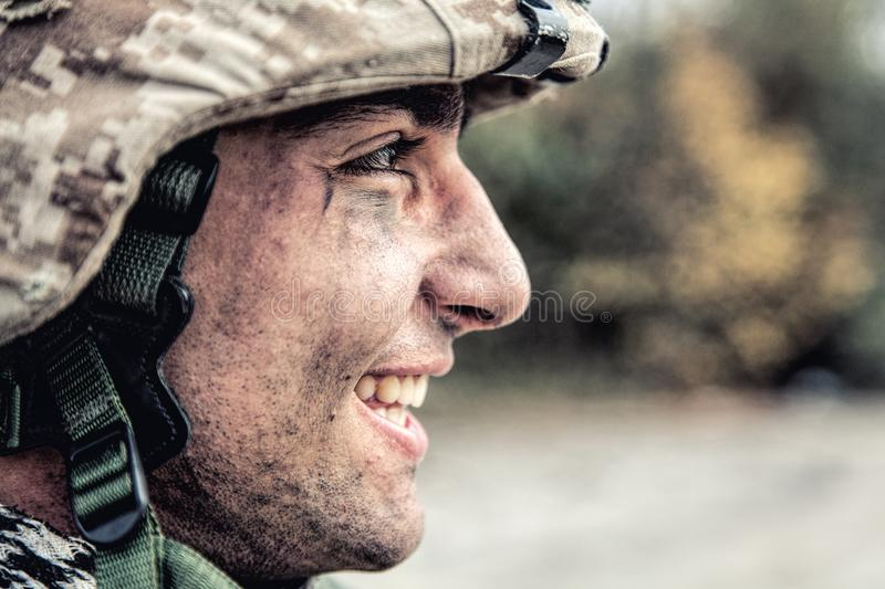 Portrait of smiling army soldier in ragged helmet. Shoulder portrait of happy smiling young soldier in battle helmet with scratches on camouflage, equipped U.S royalty free stock images
