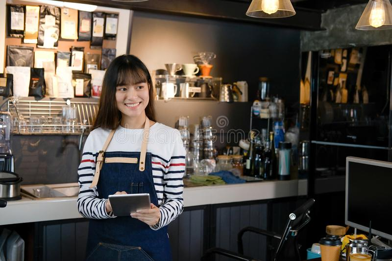 Portrait of smiling asian barista holding digital tablet at counter in coffee shop. Cafe restaurant service, food and drink indus. Portrait of smiling asian royalty free stock image
