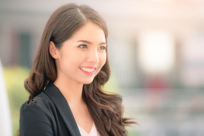 Portrait of a smiling asian businesswoman standing with arms folded on blurred city background. Business concept stock photography