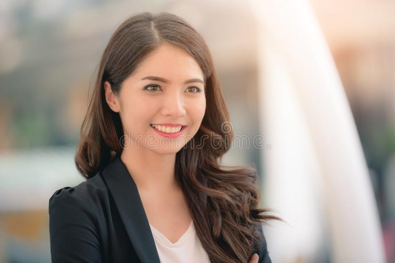 Portrait of a smiling asian businesswoman standing with arms folded on blurred city background. Business concept royalty free stock image