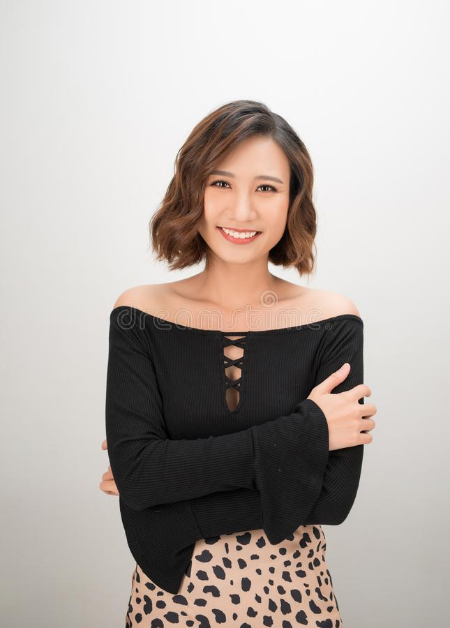 Portrait of a smiling asian businesswoman standing with arms folded and looking at camera isolated over white background royalty free stock photography