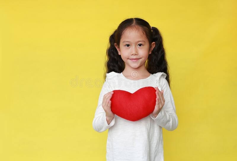 Portrait of smiling asian kid girl holding a red heart for you isolated on yellow background with copy space royalty free stock photo