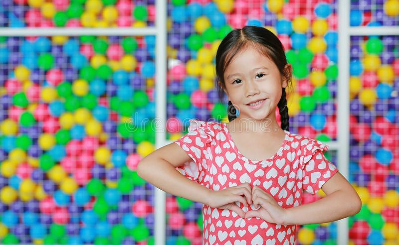 Portrait of smiling Asian little girl showing heart sign against colorful ball playground. Expresses love emotions royalty free stock photography