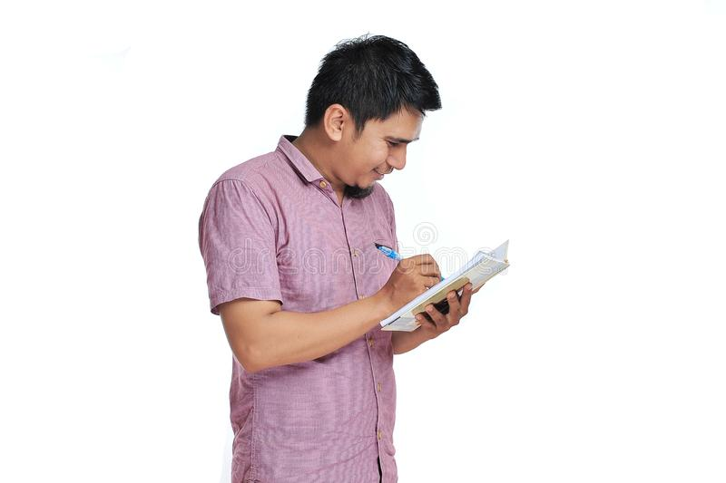 Portrait of smiling Asian male writing on his notebook with pink t-shirt royalty free stock image