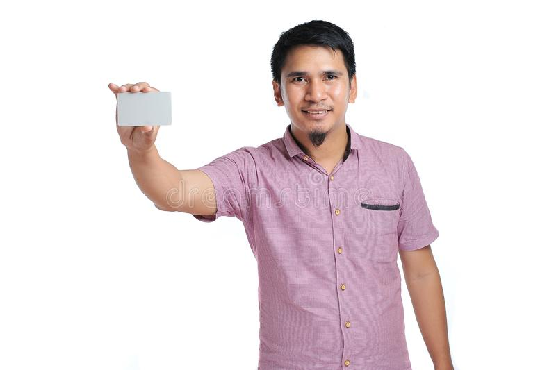 Portrait of smiling Asian man holding white blank business card royalty free stock image