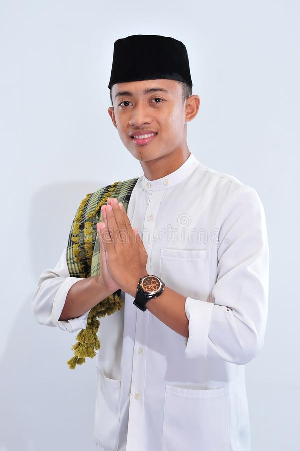 Portrait of smiling asian muslim man welcoming you royalty free stock image
