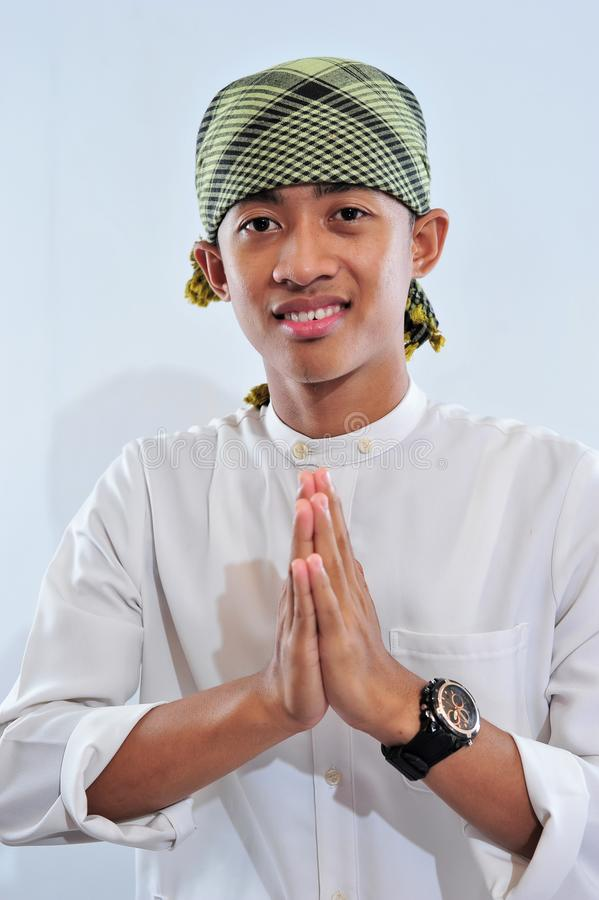 Portrait of smiling asian muslim man welcoming you stock photography
