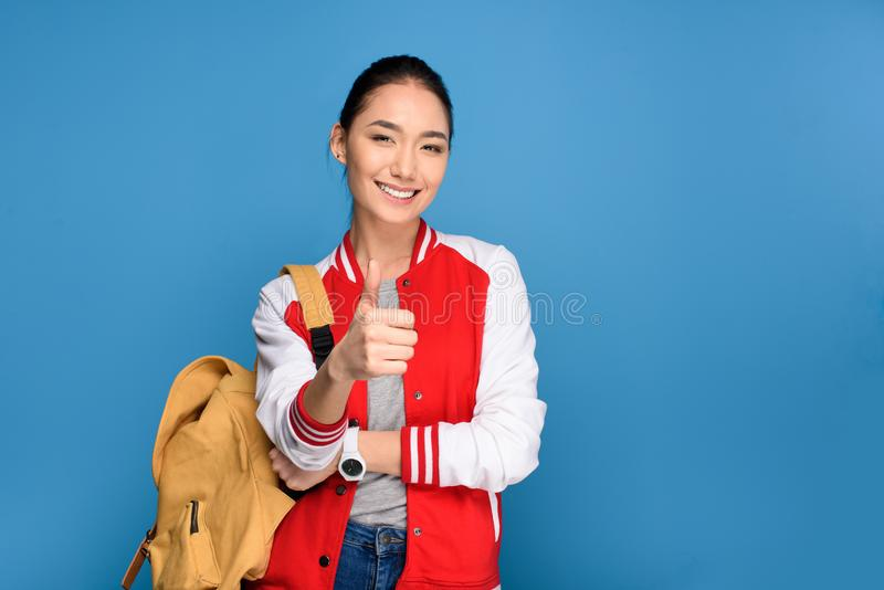 portrait of smiling asian student showing thumb up stock image