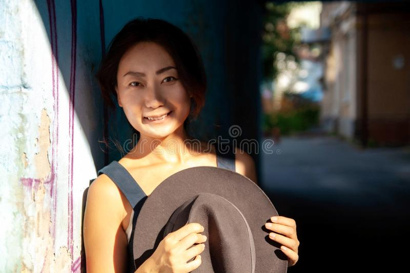 Portrait of smiling asian woman outdoors. Portrait of smiling asian woman with a black hat outdoors at sunset stock photo