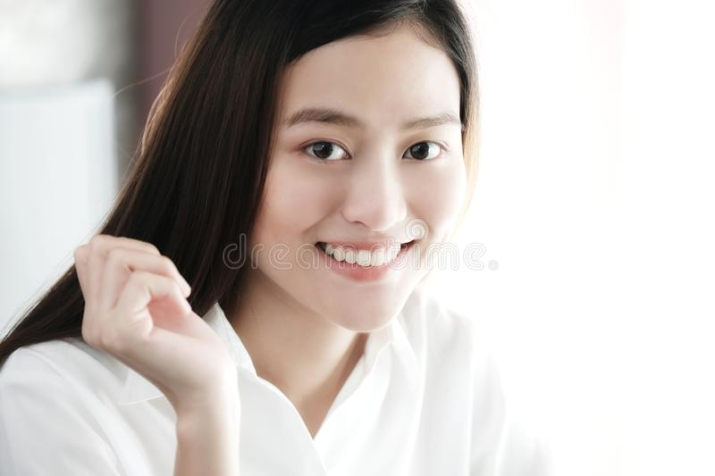 Portrait of smiling asian woman in white shirt and long hair, c royalty free stock photo