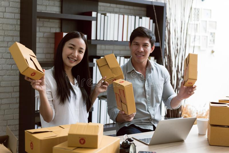 Portrait of smiling asian young woman with cardboard boxes standing in house office royalty free stock photography