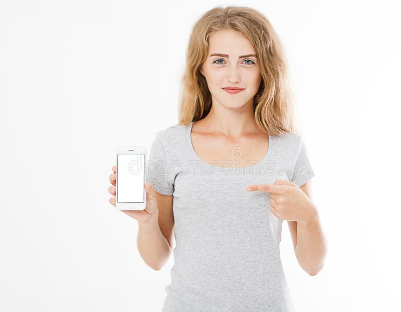 Portrait of smiling attractive, pretty, woman, girl in tshirt hold cellphone, blank screen mobilephone pointing isolated on white stock photo