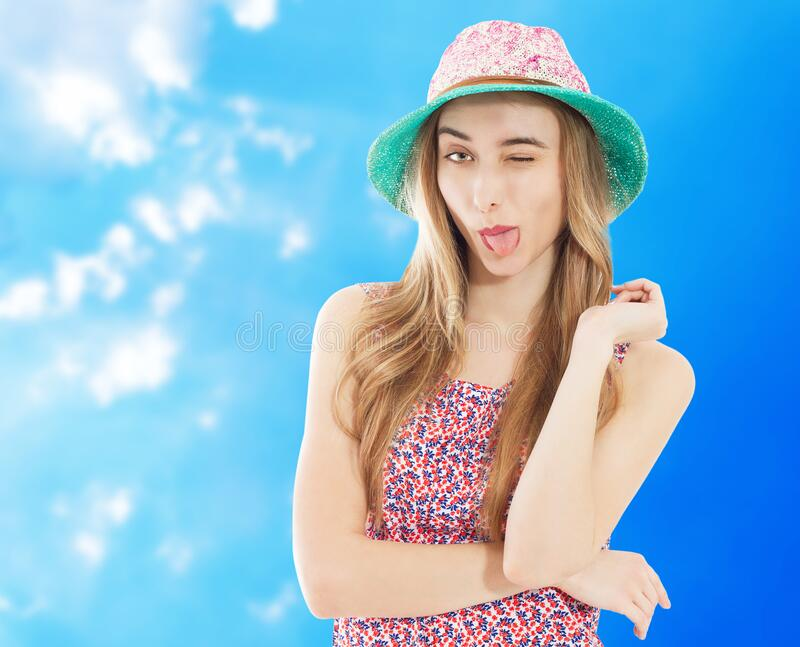 Portrait of a smiling attractive woman in summer dress and hat posing while standing and looking at camera isolated over blue royalty free stock photography