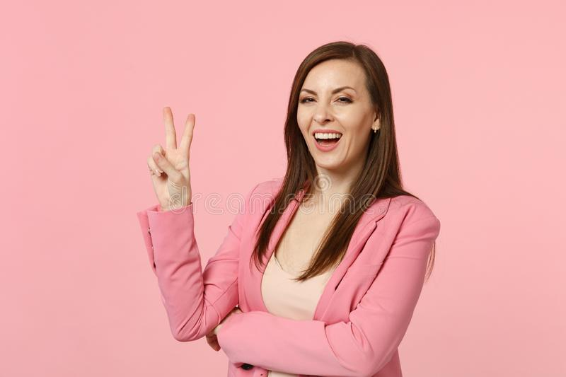 Portrait of smiling attractive young woman in jacket looking camera showing victory gesture isolated on pastel pink royalty free stock photography