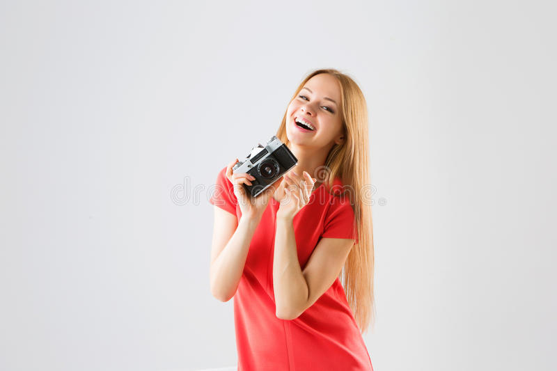 Portrait of a smiling attractive young woman taking photos using old camera. royalty free stock image