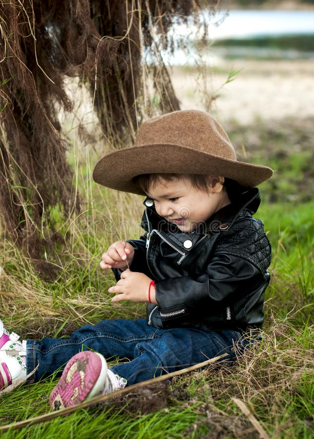 portrait of a smiling baby girl in a cowboy hat and a leather jacket in the grass stock photography